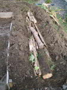 Logs in the trench waiting to be covered by turf