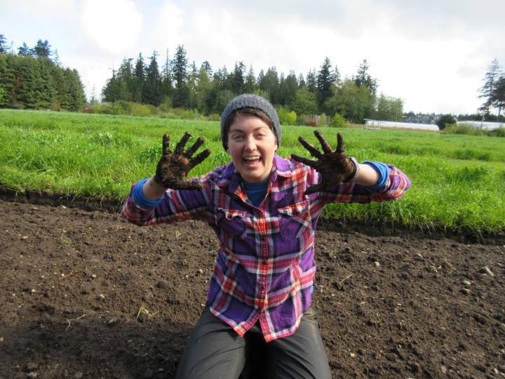 A student shows off their muddy hands at the UBC Farm Practicum in Sustainable Agriculture