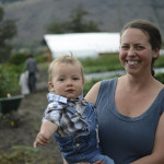 Smiling New Farmer Ashton holds her son on their certified organic farm