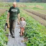 Farmer Chris Bodnar walks a row of vegetables on his farm with his daughter