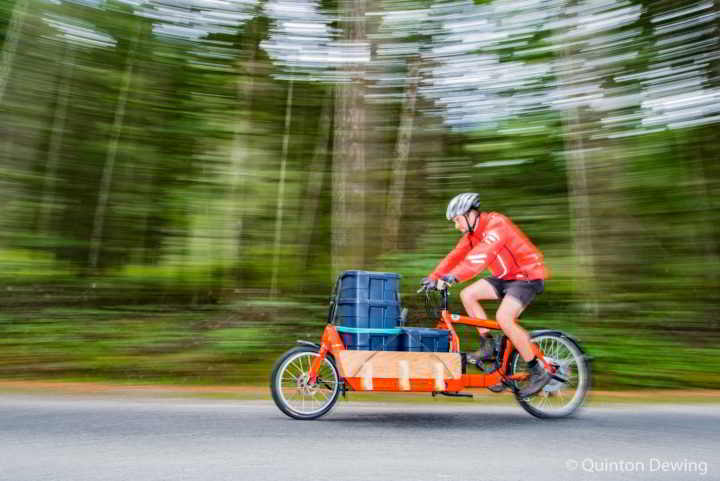 Graham Bradley races by on his red electric cargo bike delivering produce for the Gabriola Food Hub