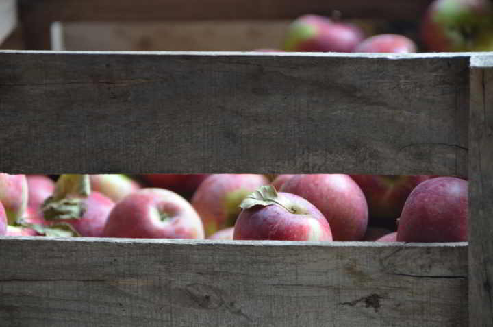 A wooden crate of rosy apples