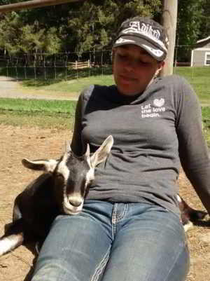 Young Agrarian Christine, a farmer looking for land, is pictured with a young goat lovingly resting it's head on her lap
