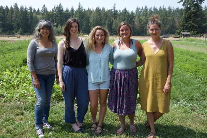 Young Agrarians Land Matchers Susheela, Darcy, Azja, Hailey, Tessa standing in a farm field