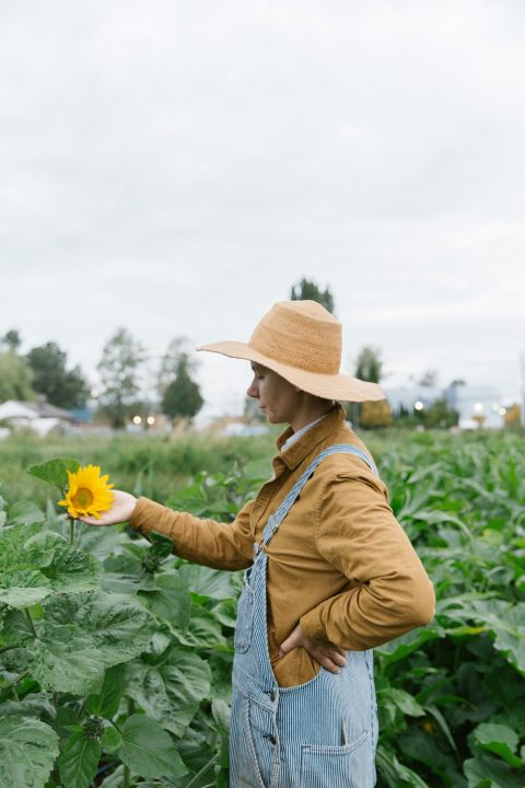 A farmer out standing in her field.