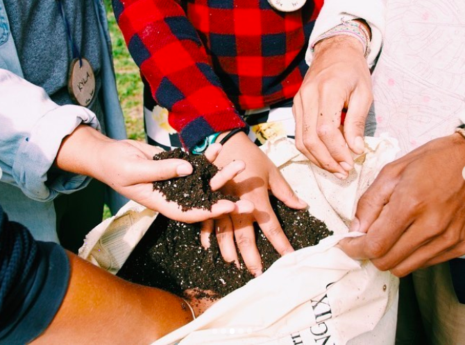 Hands holding soil at Soul Fire Farm