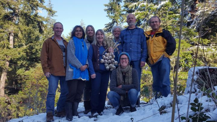 Transition land trust - Lohbrunner Community Farm Coop members and Heather Pritchard are gathered on a snow bank with a forest in the background. Heather is holding a bunch of garlic.